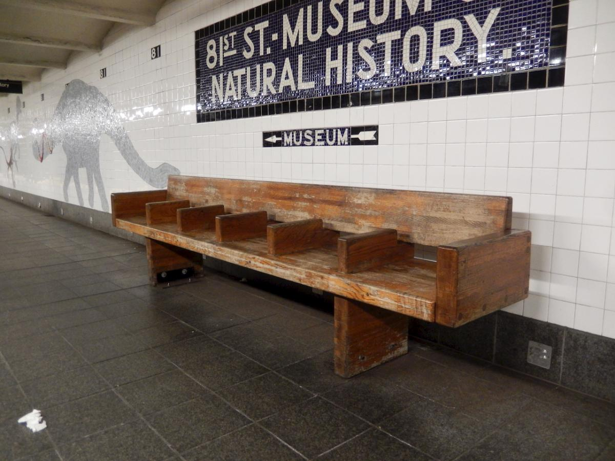A typical NYC subway bench stained with a reddish varnish.