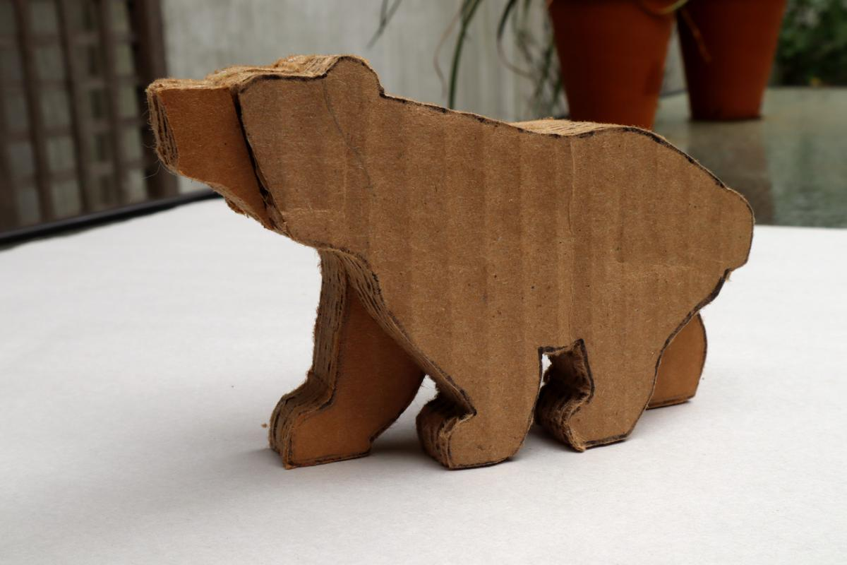 A bear carved out of layers of cardboard